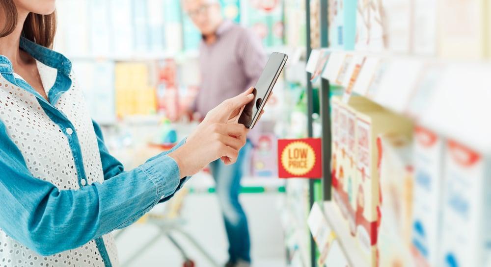 Mulher fazendo compras em supermercado utilizando tecnologia. Isso mostra o quanto o omnichannel deve fazer parte da gestão de varejo.